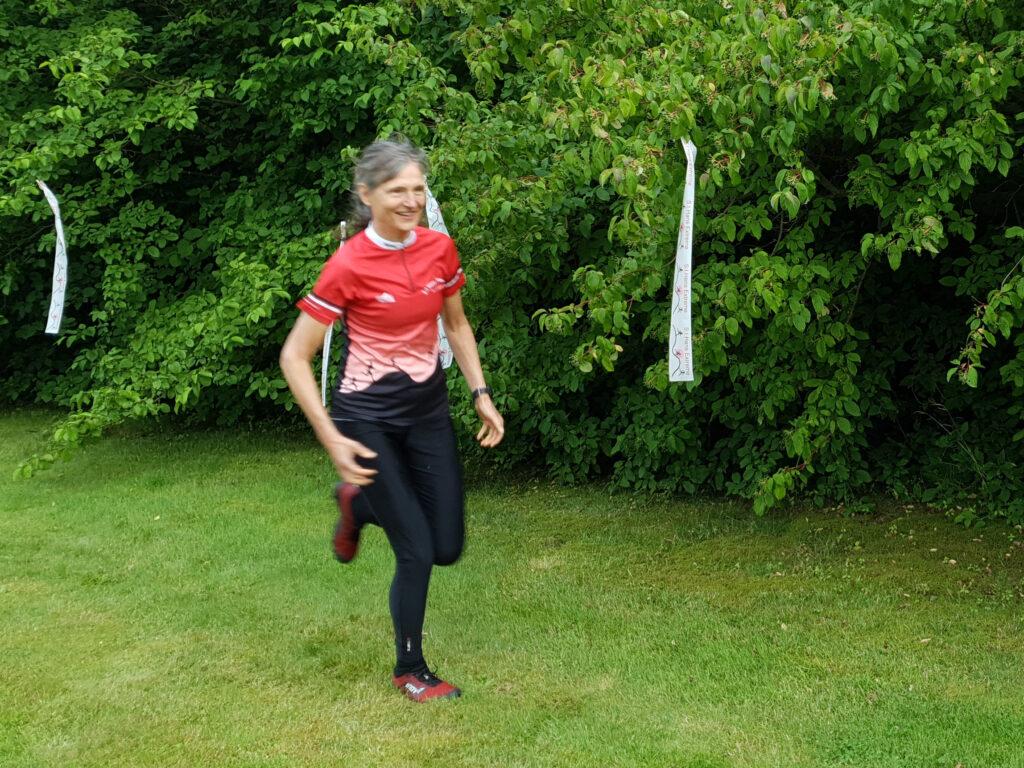 I förgrunden: Sara springandes med röda tröja med S:t Hans Extreme-tyck, svarta tights och röda löparskor på sig. I bakgrunden: träd/buskar med vita snitslar med S:t Hans Extreme-tryck.